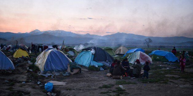 People sit by their tents in the makeshift camp at the Greek-Macedonian borders near the village of Idomeni...