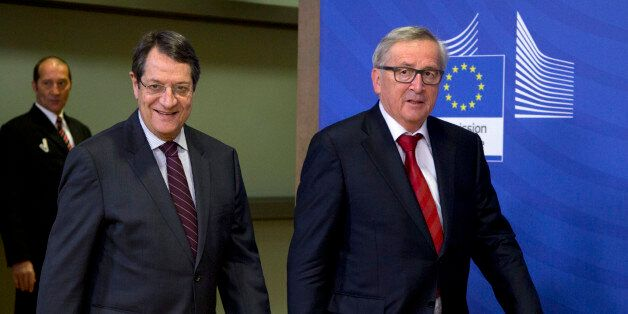 European Commission President Jean-Claude Juncker, right, walks with Cypriot President Nicos Anastasiades...