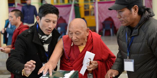 Former political prisoner 85-year-old Tibetan Palden Gyatso (C) is guided as he casts his vote to elect...