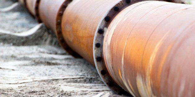 Corroded pipelines, used for land reclamation, on a beach.