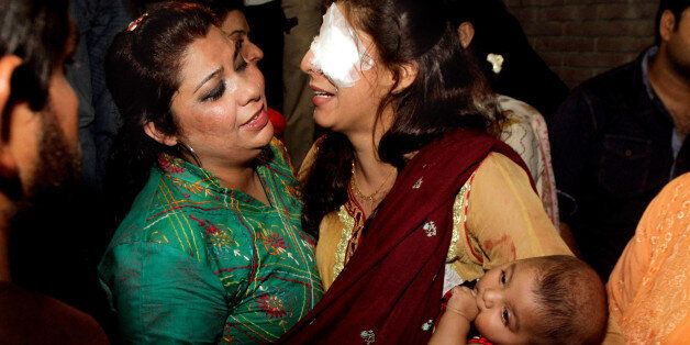 A woman injured in the bomb blast is comforted by a family member at a local hospital in Lahore, Pakistan,...