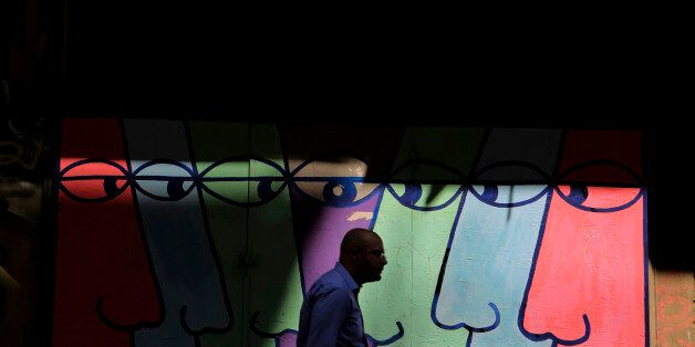 A pedestrian walks in front of a mural in central Athens, Monday, Aug. 26, 2013. In two bailout packages...