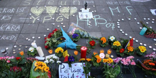 Floral tributes, candles and chalked messages of condolence sit on Beursplein square in Brussels, Belgium,...