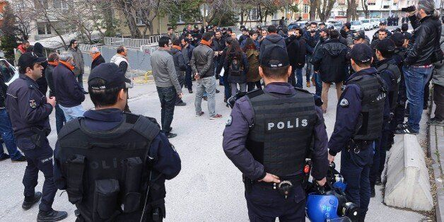 Turkish police officers circle left wing partisans as they demonstrate against Turkish government and...