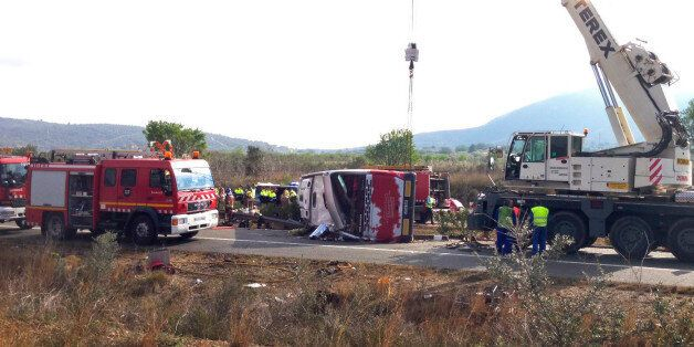 Emergency services personnel stand at the scene of a bus accident crashed on the AP7 highway that links...