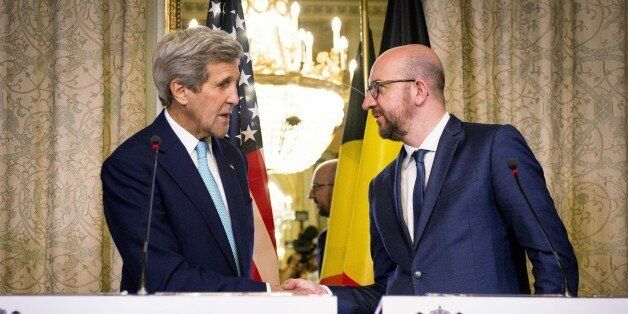 US Secretary of State John Kerry (L) shakes hands with Belgian Prime Minister Charles Michel during a...