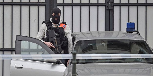An armed special police officer expects suspect Salah Abdeslam to arrive at a justice building in Brussels,...