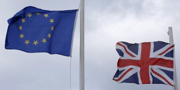 The British Union Flag, right, and the flag of the European Union (EU) fly from flagpoles outside a hotel...