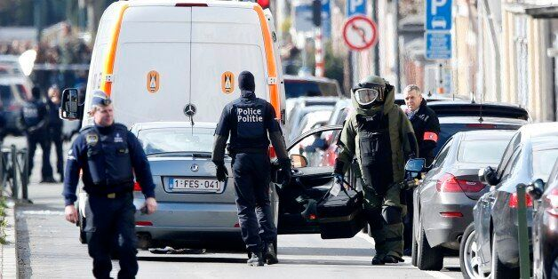 A member of emergency services wearing protective clothing, at right, investigates the scene in Schaerbeek,...