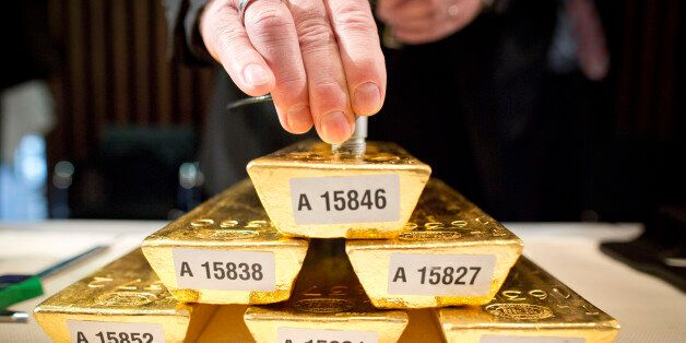 An employee of the German Federal Bank checks the core of a bar of gold during a press conference at...