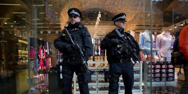 Armed British police officers stand guard after Eurostar services were suspended on the Brussels route...