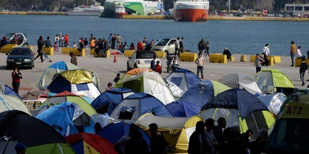 People gather at the Athens' port of Piraeus, where over 5,000 refugees and migrants stay, on Monday,...