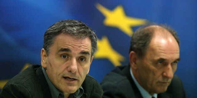 Greece's Finance Minister Euclid Tsakalotos, left, speaks during a news conference as Economy Minister...