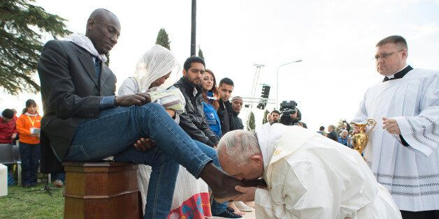 Pope Francis kisses the foot of a man during the foot-washing ritual at the Castelnuovo di Porto refugees...