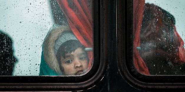 A migrant girl presses her nose agains a bus window during a rainfall on a road, north of Idomeni, Greece,...
