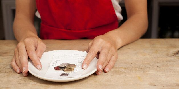 Close up of waitress with bill and gratuity at kitchen