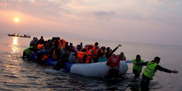 Volunteers help migrants and refugees on a dingy as they arrive at the shore of the northeastern Greek...