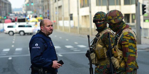 Policemen and soldier stand guard at the entrance of a security perimeter set near Maalbeek metro station,...