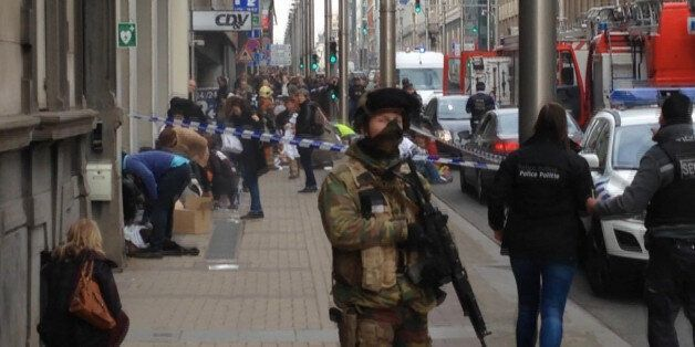 In this image taken from TV an armed member of the security forces stands guard as emergency services...