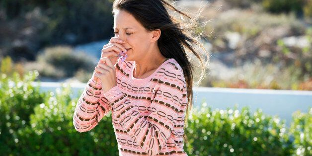 Woman sneezing while smelling a flower