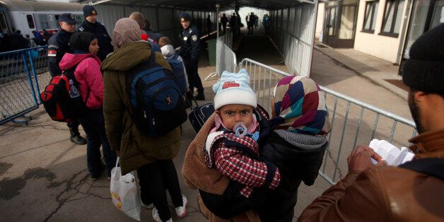 Migrants wait to board a train at the train station in Sid, about 100 km (62 miles) west from Belgrade,...