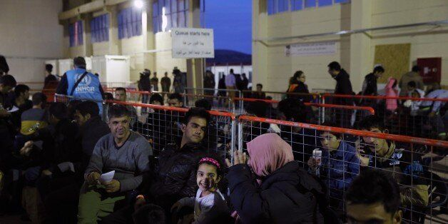 Refugees and migrants wait for the procedures at a registration and hospitality center, know as a hotspot,...