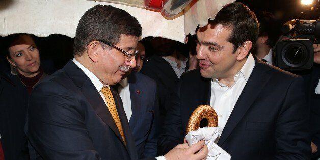 IZMIR, TURKEY - MARCH 08: Turkish Prime Minister Ahmet Davutoglu (L) offers a traditional Turkish bagel...