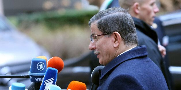 Turkish Prime Minister Ahmet Davutoglu, center, speaks with the media as he arrives for an EU summit...