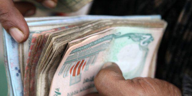 A vender counts bank notes at a market in Dhaka, Bangladesh, on Monday, Jan. 9, 2012. Bangladesh's central...