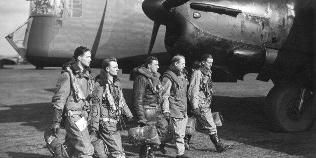 World War II British airforce bomber crew walking in front of aircraft.From left to right: Observer,...