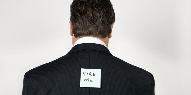 Man wearing a suit with 'hire me' note on his
