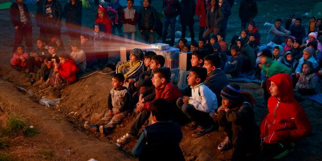 Children watch a cartoon movie in a field at the northern Greek border station of Idomeni, Saturday,...