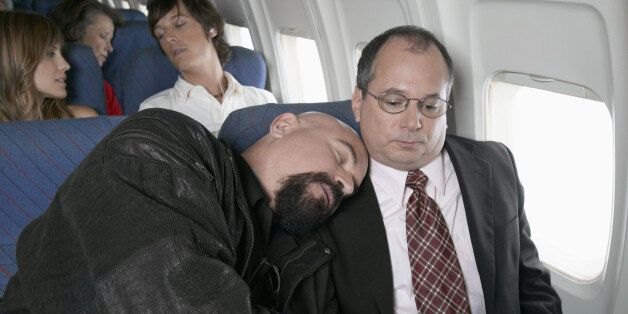 Businessman Sitting in an Aeroplane Trapped by a Man Sleeping by His Side