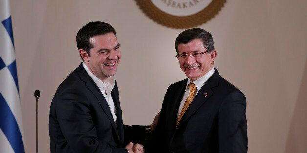 Turkey's Prime Minister Ahmet Davutoglu, right, shakes hands with Greece's Prime Minister Alexis Tsipras,...