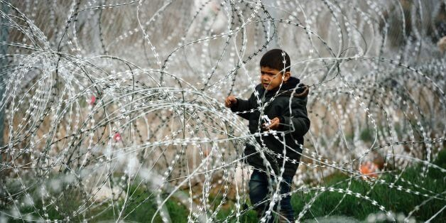 TOPSHOT - A child stands among a razor-topped fence close to the gate at the Greek-Macedonian border...