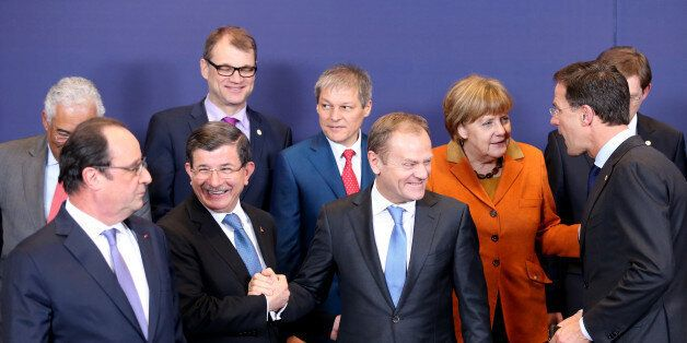 European Council President Donald Tusk, front center, shakes hands with Turkish Prime Minister Ahmet...