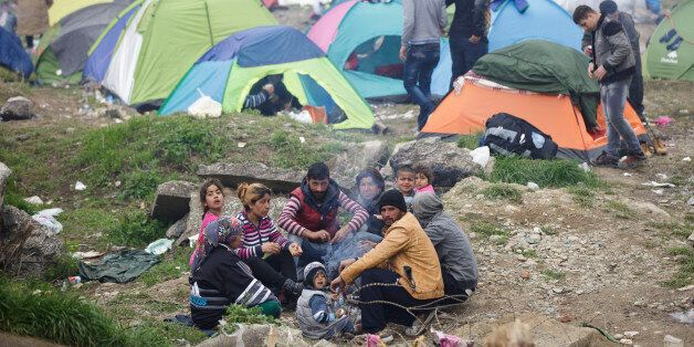 A migrant family gather around a fire, at the northern Greek border station of Idomeni, Monday, March...