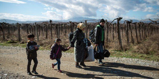 A migrant family crosses the Greek-Macedonian border near the town of Gevgelija, on February 14, 2016....