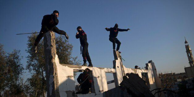 Palestinian youth, members of a Gazan martial art group, perform their ninja-like skills at ruins of...