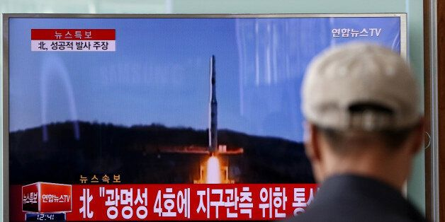 People watch a television screen showing a news broadcast on North Korea's long-range rocket launch at...