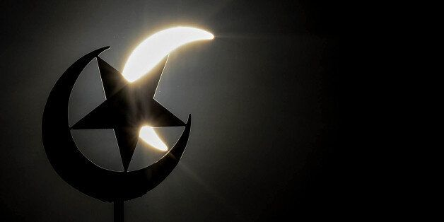 A general view shows a partial solar eclipse behind a star and crescent symbol atop a mosque in Kuala...