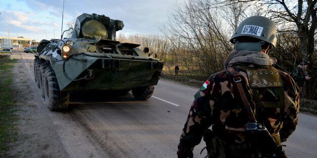 Hungarian soldiers control with their armoured car the metal fence-saved border line at Asotthalom border...