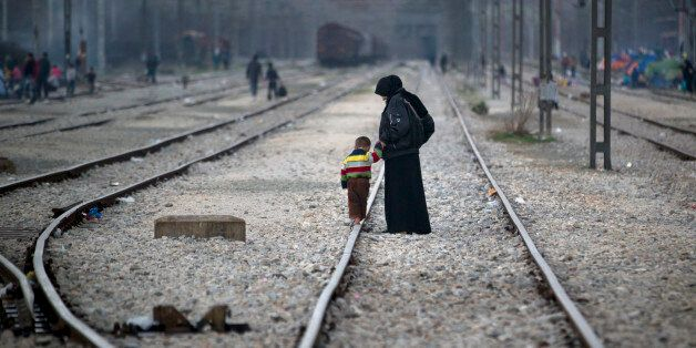 A woman holds the hand of a toddler walking on a railway track at the northern Greek border station of...
