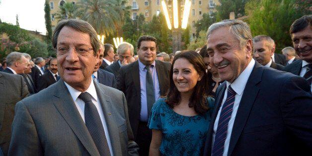 Cyprus' president Nicos Anastasiades, left, and Turkish Cypriot leader Mustafa Akinci, right, arrive...