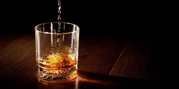 Scotch or bourbon whiskey (or whisky) being poured into a glass with dramatic studio lighting and a black