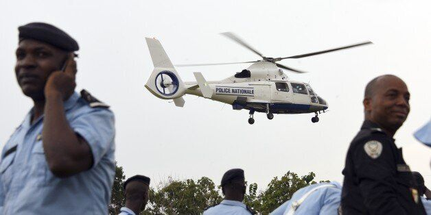A helicopter handed over by the national council of security hovers over Ivorian policemen at the police...
