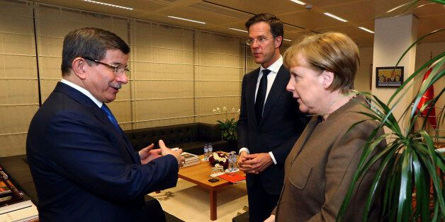 Turkey's Prime Minister Ahmet Davutoglu, left, listens to Germany's Chancellor Angela Merkel, right as...