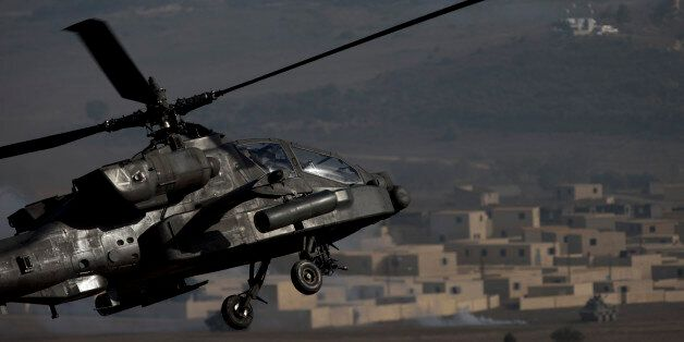 A US AH-64 Apache flies over the combat zone during a NATO military demonstration in Zaragoza, Spain,...
