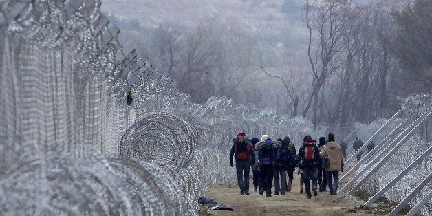 Refugees and migrants, who entered Macedonia from Greece illegally, walk between the two lines of the...