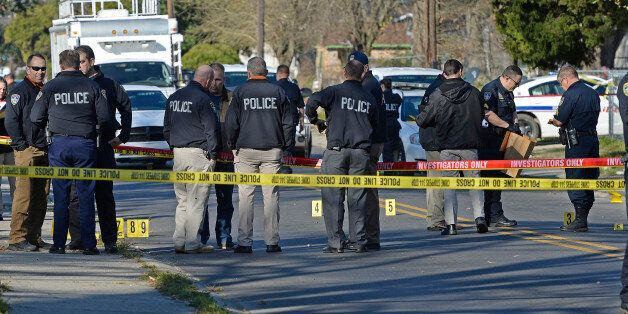 Officers investigate the scene of a shooting in Baton Rouge, La., Saturday, Feb. 13, 2016. Police officers...
